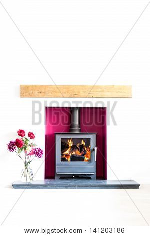 Wood burning stove with blazing log fire in a magenta coloured recess in a white room with a vase of dahlia flowers. High key