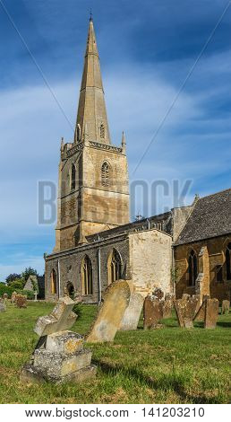 English Country Church with Graveyard and Tall Spire on Summers Day against blue cloud studded sky