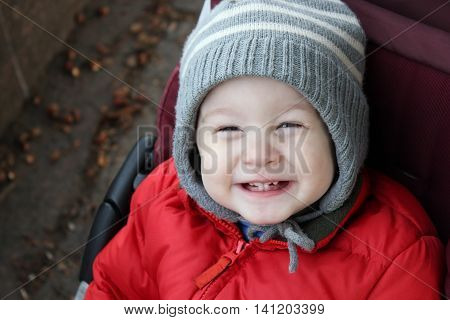 Baby boy giggles siting in stroller. Boy is so happy and shows baby teeth