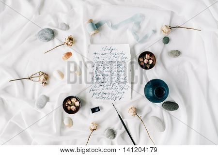 Flat lay wedding invitation cards dry roses brush stones shells spool with ribbon menu carte on white textile. Overhead view.