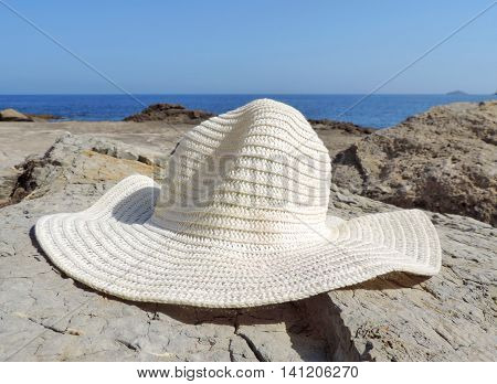 Summer hat on the seas. White hat and seascape.