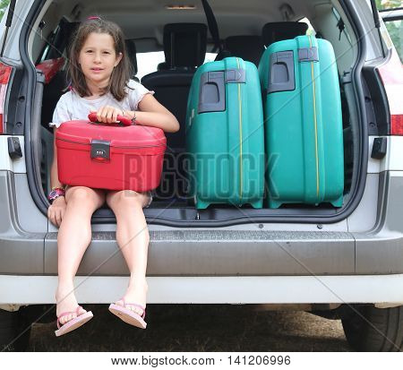 Little Girl With Brown Hair Long Loads The Suitcase In The Trunk