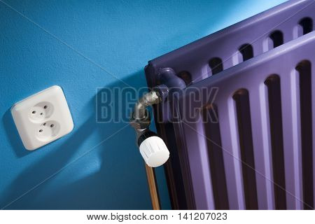 Thermostat on a purple central heating radiator and a blue wall with power point