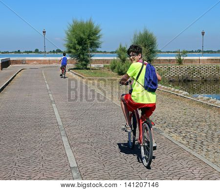 two young brothers ride near the lagoon of Venice