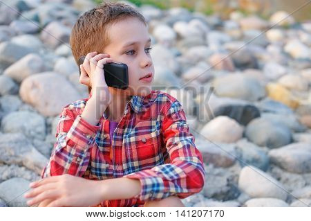 kid talking on the phone sitting on the rocks. boy during a conversation on the phone distracted by something. look away