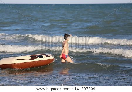 brave boy with the dinghy on choppy sea in summer