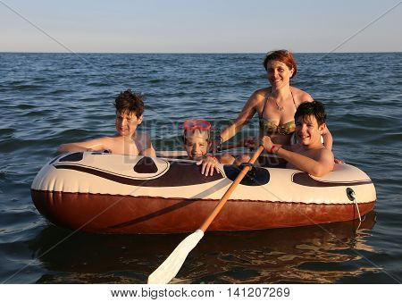 three brothers with mom on the dinghy sailing on the sea in summer