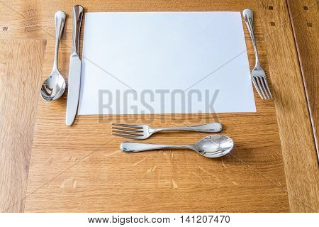 Place setting on a wooden table with knife fork soupspoon and desert cutlery