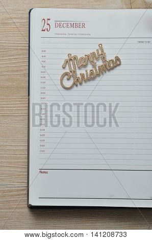 Diary open on the 25th of December decorated with merry christmas