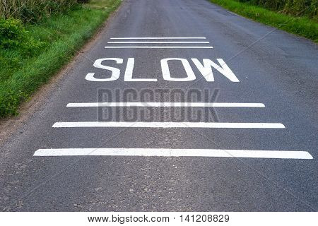 Slow Sign freshly painted on road with lines above and below for emphasis