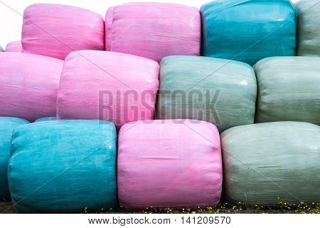Stack of pink blue and green silage bags