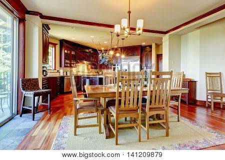 View Of Honey Color Dining Table Set With Kitchen In The Background.