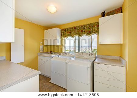 Old Laundry Room With White Cabinets And Yellow Walls.