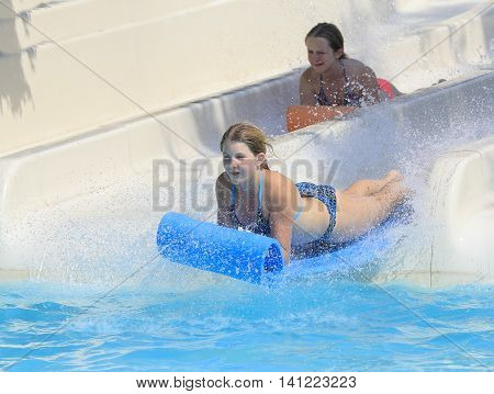 Rhodes Greece-August 1 ,2016: Two girl on the mat racer slide.Mat racer slide is very popular for young people in the Water Park. Water Park is located on the island of Rhodes in Greece and one of the most largest in Europe and is a very popular place
