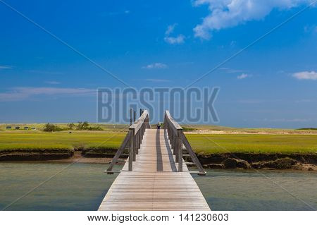 Walkway to the dunes wooden walkway extends over marshland toward the distant dunes and ocean In Sandwich Cape Cod Massachusetts USA