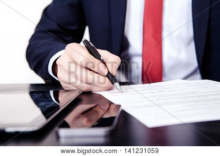 The man in the red tie signs contract. On the table lies a tablet and phone