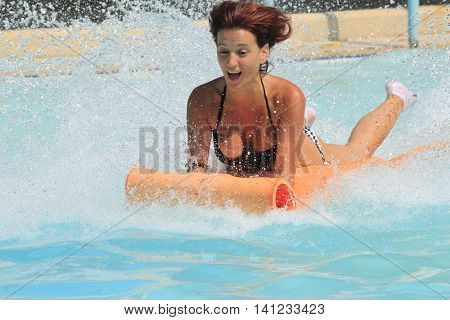 Rhodes Greece-August 1,2016:Girl on the mat racer slide.Mat racer slide is very popular for young people in the Water Park. Water Park is located on the island of Rhodes in Greece and one of the most largest in Europe and is a very popular place