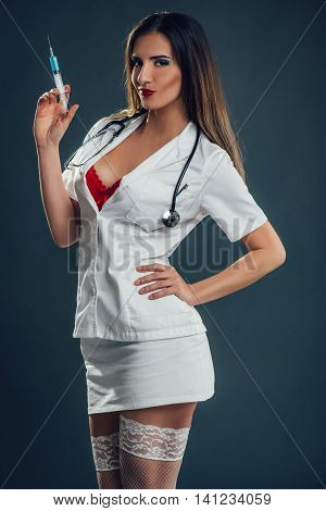Beautiful smiling sexy nurse standing and holding injection. Looking at camera.