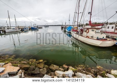 Fishing boats reflect in the St Helens harbor, Georges Bay, Tasmania, Australia. St Helens is the most important city of the northeast coast and is famous for the Bay of Fires