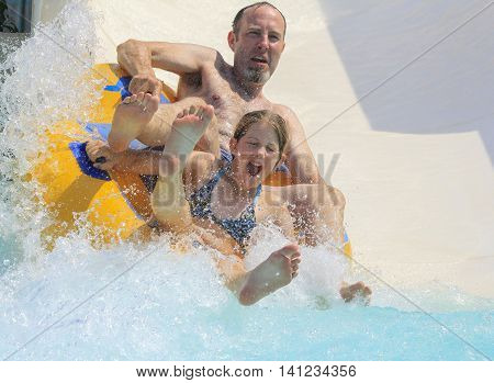 Rhodes Greece-August 1 2016:Father and  daughter on the rafting slide in the Water park.Rafting slide is one of many popular game for adults and children in park. Water Park is located on the island of Rhodes in Greece and one of the most largest in Europ