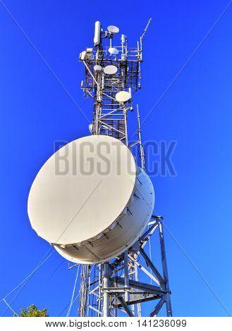 Communication antenna tower on blue sky closeup