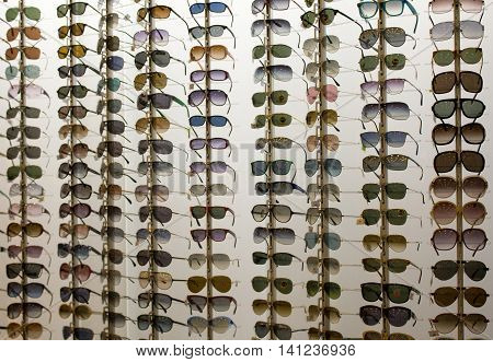 Exhibitor of glasses consisting of shelves of fashionable glasses shown on a wall.