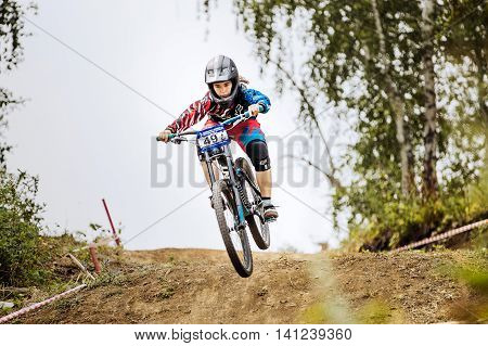 Magnitogorsk Russia - July 23 2016: jump over mountain girls extreme athlete bike during National championship downhill