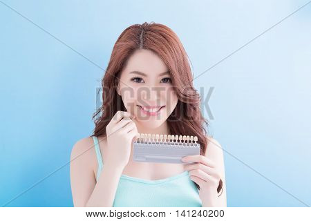 Beautiful young woman with health teeth and hold teeth whitening tool. Isolated over blue background asian beauty