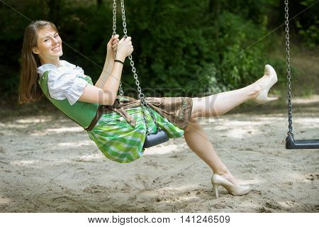 bavarian woman in dirndl sitting on swing outdoors