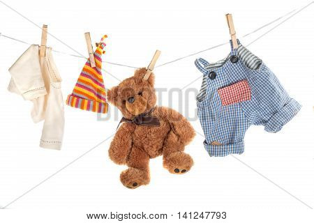 Teddy bear hanging on clothesline with clothes