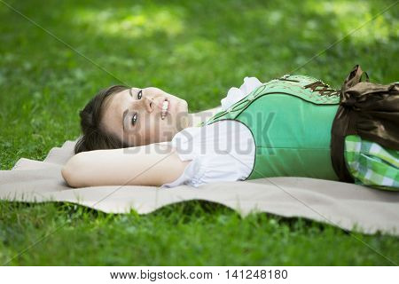 young woman in dirndl lying on blanket in grass