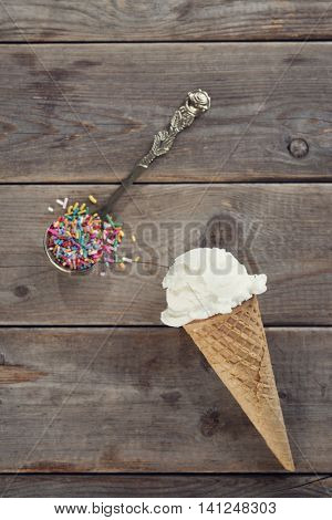 Top view single scoop scoop vanilla ice cream in waffle cone with spoon of color rice on wood background.