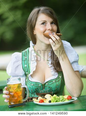 young bavarian woman in dindl sitting outdoors at beergarden and eats