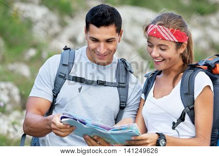 Tablet computer - couple hiking using internet and tablet computer pc guide book app on hike in Zion National Park. Interracial active hiker couple, Asian woman, caucasian man trekking in Utah, USA
