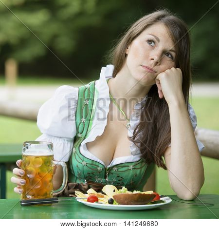 young woman in dirndl sitting at beer garden with food and beer and looking bored