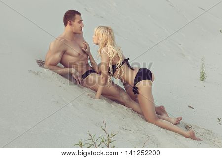 Man with athletic body lying on the sand blonde woman touches his muscle.