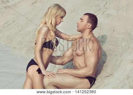 Man and woman passionately look into each other's eyes they are on the sandy beach.