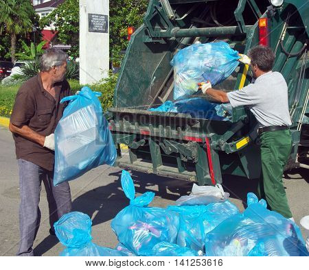Lazarevskoe, Sochi, Russia - June 27, 2014: Workers charged with garbage in a garbage truck on city streets Lazarevskoye