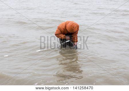 Fisherman in orange overalls checking his net
