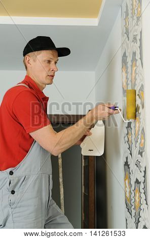 Worker adhesive arras. He presses for better wallpaper adhesive using a roller and scraper.