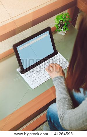 Girl sits at a table with a laptop. Telework concept. Copy space. top view. mockup