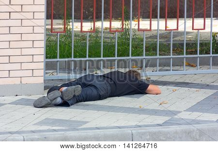 KRASNODAR RUSSIA - AUGUST 4 2016: a Drunk homeless man lying on the sidewalk