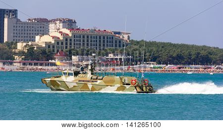 military boat at full speed makes blank volley of guns on the city beach. Russia Gelendzhik