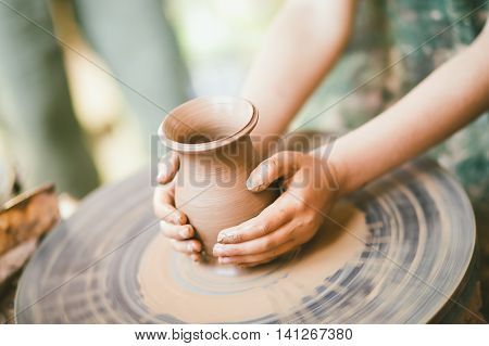 Apprentice learning clay crafting, child hands holding a clay pot