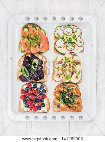 Sweet and savory breakfast toasts assortment. Sandwiches with fruit, vegetables, eggs and smoked salmon on white baking tray over white painted wooden background, top view