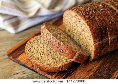 Sliced Whole Grain Bread With Nutritious Flax Seeds On Wooden Board