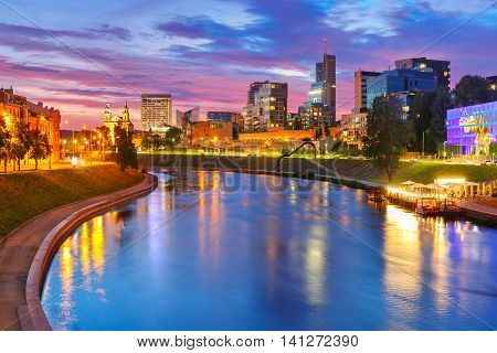 Night cityscape with Neris river, church and skyscrapers of New Center of Vilnius, Lithuania, Baltic states.