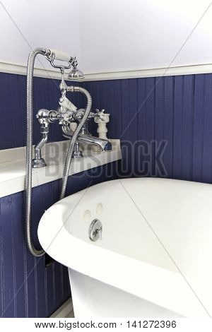 White Tub With Antique Hardware, Blue Wood Wall.