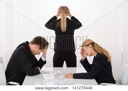 Sad Young Businesspeople With Hands On Head In Office