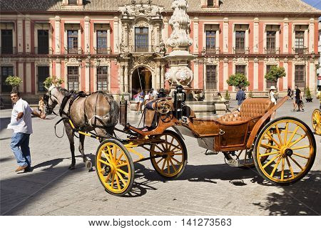 SEVILLE, SPAIN - September 13, 2015: Many typical old horse driven carriages wait for the tourists business by the Cathedral on September 13, 2015 in Seville, Spain